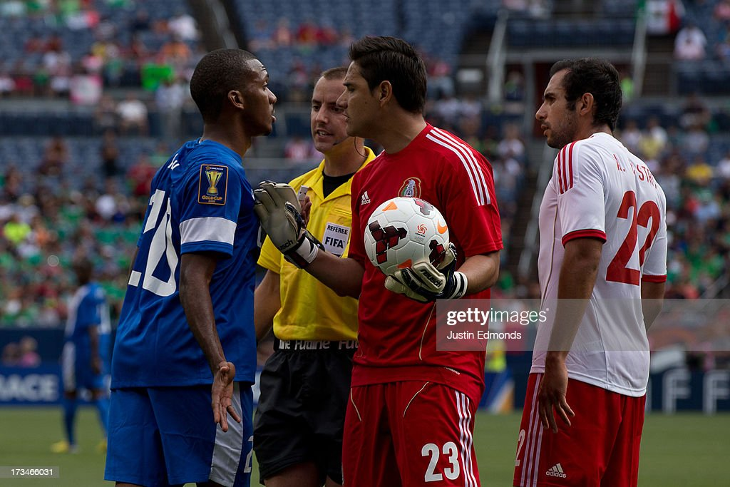 Stephane Abaul #20 of Martinique shares his frustration with goalkeeper Moises Muñoz #23, Alejandro Castro #22 and referee Mark Geiger during the second half of a CONCACAF Gold Cup match at Sports Authority Field at Mile High on July 14, 2013 in Denver, Colorado. Mexico defeated Martinique 3-1.