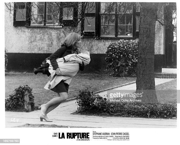 Stephane Audran running while holding her injured son in a scene from the film 'The Breach' 1970