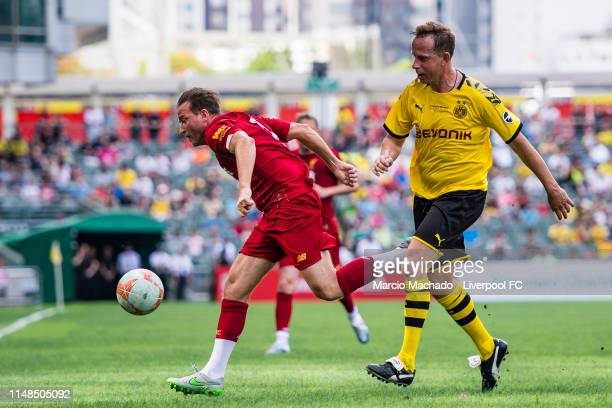 Stephane Henchoz of Liverpool FC fights for the ball with Jorg Heinrich of Borussia Dortmund during the match between during the match between...