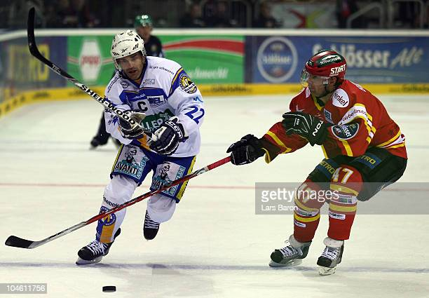 Stephane Julien of Muenchen is challenged by Mark Murphy of Duesseldorf during the DEL match between DEG Metro Stars and EHC Muenchen at ISS Dome on...