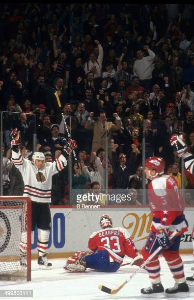 Stephane Matteau of the Chicago Blackhawks celebrates a goal as goalie Don Beaupre and Sylvain Cote of the Washington Capitals look dejected on...