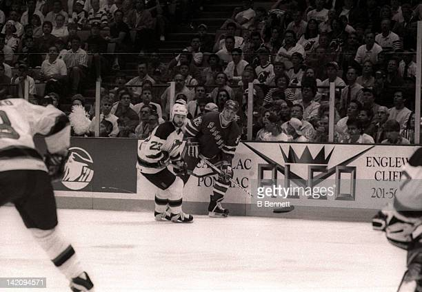 Stephane Matteau of the New York Rangers and Bruce Driver of the New Jersey Devils skate along the boards during Game 6 of the Eastern Conference...