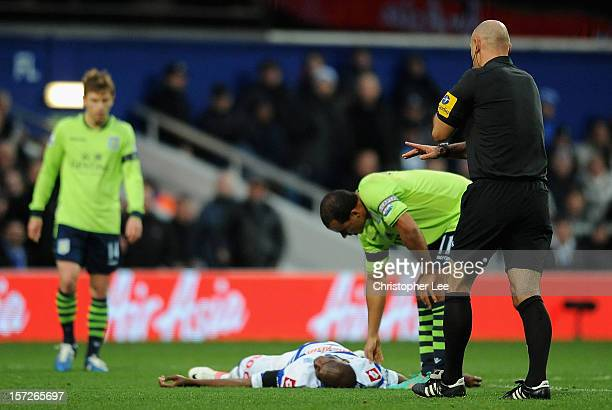 Stephane Mbia of Queens Park Rangers lies injured on the pitch during the Barclays Premier League match between Queens Park Rangers and Aston Villa...