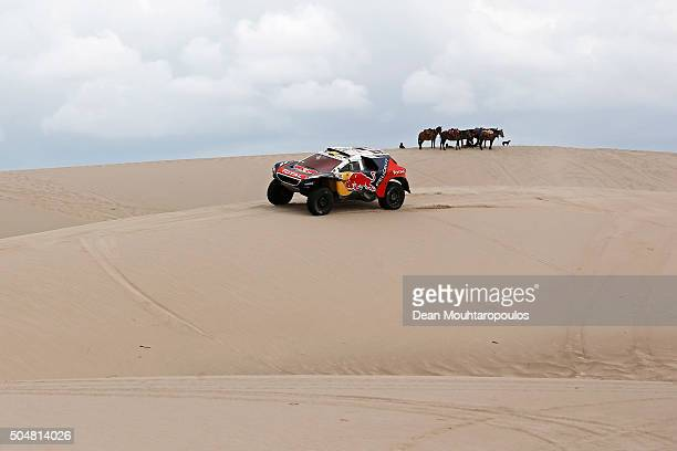Stephane Peterhansel of France and Paul Jean Cottret of France in the PEUGEOT 2008 DKR for TEAM PEUGEOT TOTAL SOUTH AFRICA pass a group or team of...
