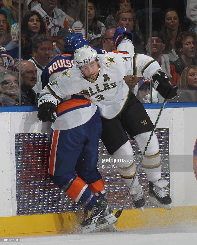 Stephane Robidas #3 of the Dallas Stars hist Matt Moulson #26 of the New York Islanders at the Nassau Coliseum on October 9, 2010 in Uniondale, New York.