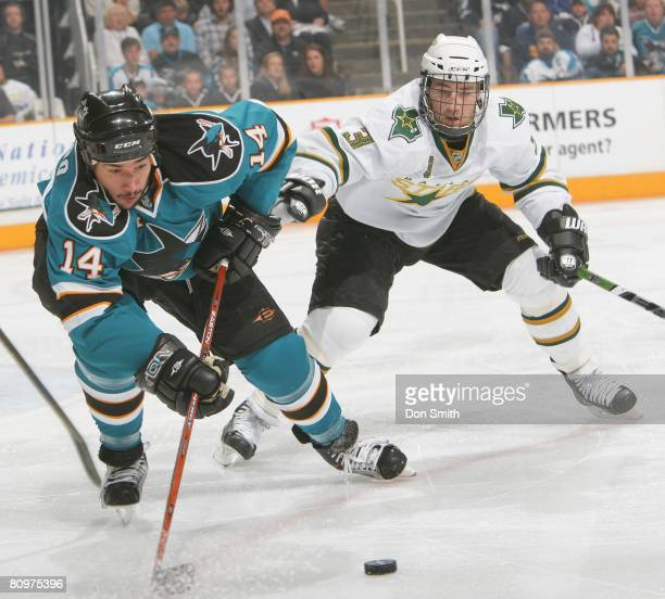 Stephane Robidas of the Dallas Stars reaches for Jonathan Cheechoo of the San Jose Sharks as he goes for the puck during game five of the 2008 NHL...