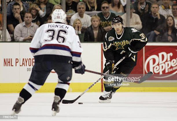 Stephane Robidas of the Dallas Stars skates with the puck as Jannik Hansen of the Vancouver Canucks defends during game three of the 2007 NHL Western...