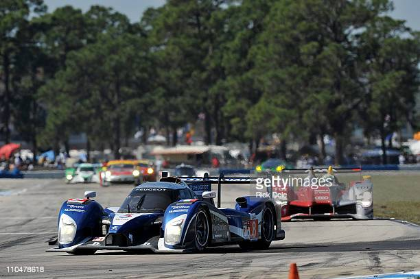 Stephane Sarrazin of France drives the Peugeot Sport Total Peugeot 908 and leads Allan McNish driving the Audi Sport Team Joest Audi R15+ during the...