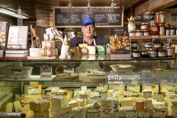 Stephane Strouk, chief executive officer of the Monsieur Marcel Bistro, stands for a photograph behind a case of European cheeses at his store in Los...