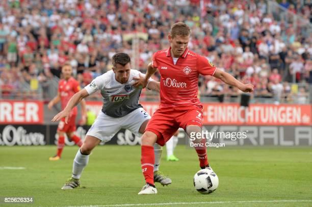 Stephane Tritz of Muenster challenges Felix Mueller of Wuerzburgduring the 3 Liga match between FC Wuerzburger Kickers and SC Preussen Muenster at on...