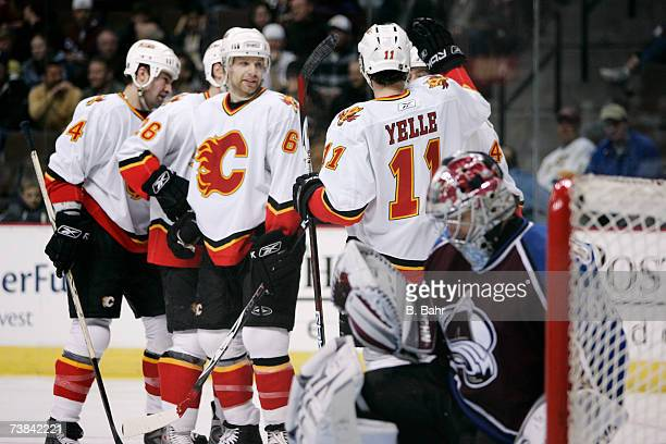 Stephane Yelle of the Calgary Flames congratulates Alex Tanguay on his assist on a goal by Marcus Nilson against goalie Jose Theodore of the Colorado...
