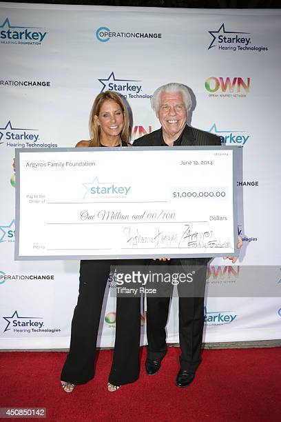 Stephanie Argyros presents founder of Starkey Hearing Foundation Bill Austin with a one million dollar check at the premiere of Operation Change at...