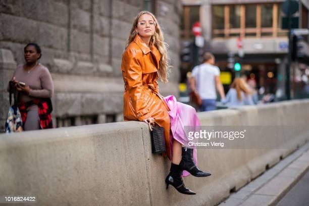 Stephanie Broek wearing orange vinyl coat seen outside Epilogue during Oslo Runway SS19 on August 14 2018 in Oslo Norway