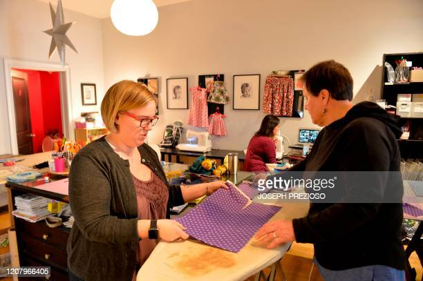 Stephanie Cave and Karen Foley prepare fabric to be cut up as part of the first step in creating masks at Stitch House in Dorchester Massachusetts on...