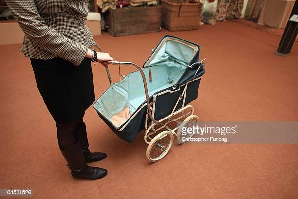 Stephanie Cliffe from Chatsworth House wheels away a Marmet canvas pram at valued at 15 GBP the cheapest items for sale in the Chatsworth Attic Sale...