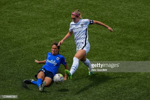 Stephanie Cox of OL Reign attempts to kick around Morgan Weaver of Portland Thorns FC during a game on day 8 of the NWSL Challenge Cup at Zions Bank...