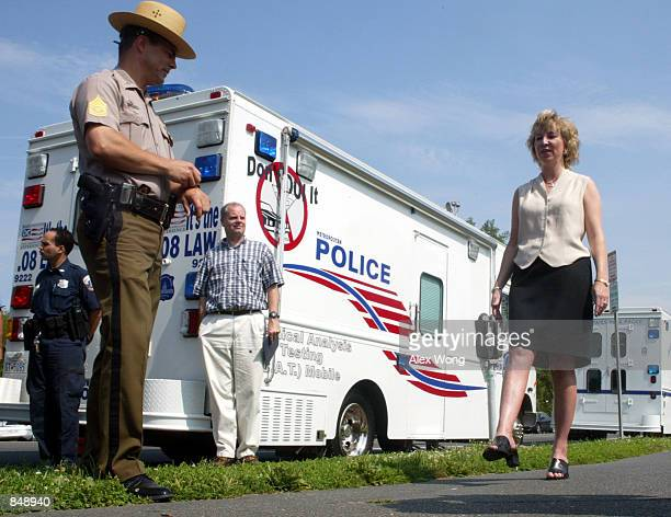 Stephanie Hancock of the US Department of Transportation holds up her leg as First Sergeant Tom Woodward of Maryland State Police looks on during a...