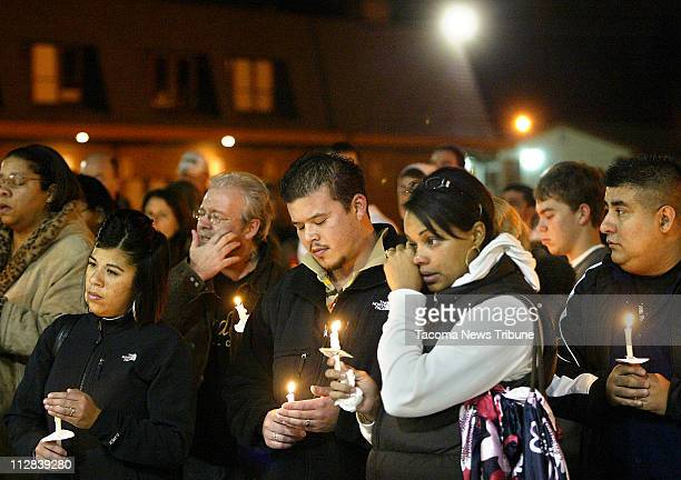 Stephanie James second from right and wife of a Lakewood Police officer wipes a tear during a candlelight vigil held at the Champions Centre for the...
