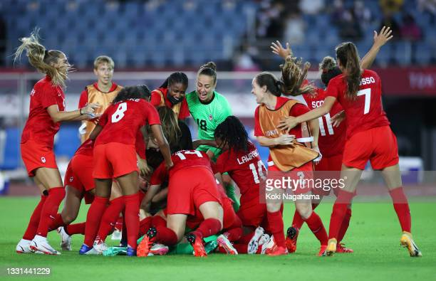 Stephanie Labbe of Team Canada celebrates victory with teammates after saving the Team Brazil fifth penalty taken by Rafaelle in a penalty shoot out...