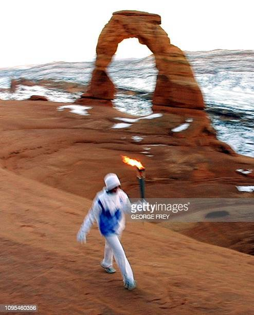 Stephanie Laree Spann runs the Olympic torch in the bowl of Delicate Arch in Arches National Park near Moab Utah 04 February 2002 The torch arrived...