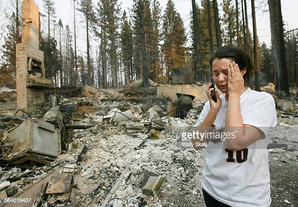 Stephanie Spees cries while talking on the cell phone next to her burned down home on Mt Diablo in South Lake Tahoe Monday