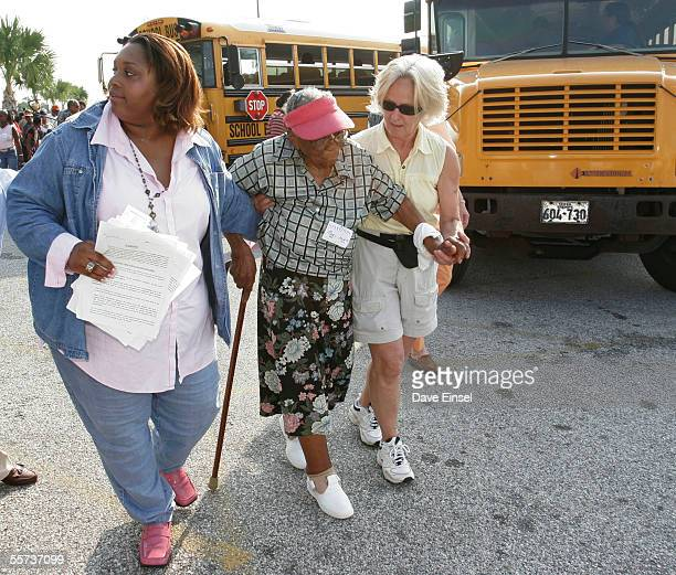 Stephanie Thomas of the Galveston Housing Authority and Marianne Cassells help Mary Jones to board an evacuation bus at the Island Community Center...