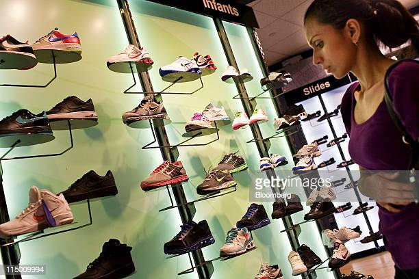 Stephanie Vargas looks at Nike Inc footwear at a Modell's store in New York US on Wednesday June 1 2011 Retailers are poised to boost prices on...