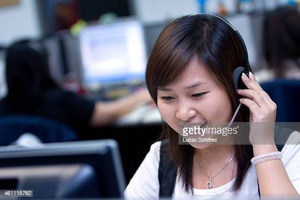 Stephanie Xia answers clients' phone calls at Citigroup Data Processing Center on May 26 2010 in Guangzhou Guangdong province China