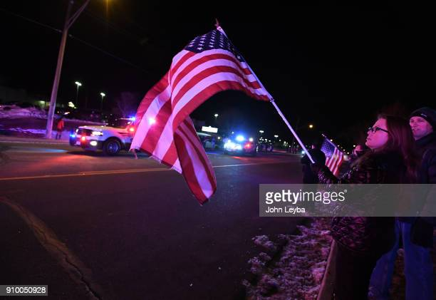 Stephannie Anderson of Brighton holds a flag as she pays her respect to fallen Adams County Sheriff's deputy who was gunned down A flag hung down...