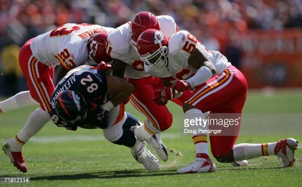 Stephen Alexander of the Denver Broncos is taken down by Patrick Surtain Tamba Hali and Derrick Johnson of the Kansas City Chiefs during NFL action...