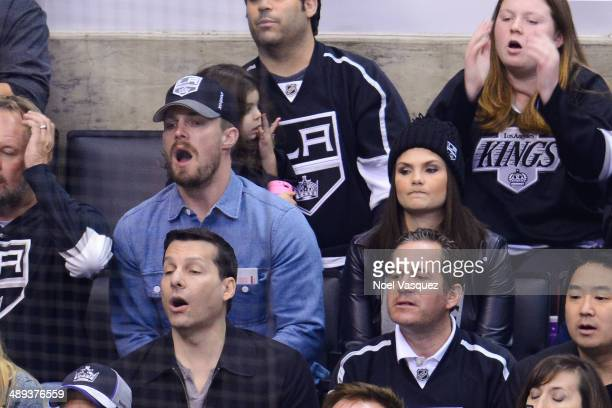 Stephen Amell and Cassandra Jean attend an NHL playoff game between the Anaheim Ducks and the Los Angeles Kings at Staples Center on May 10 2014 in...