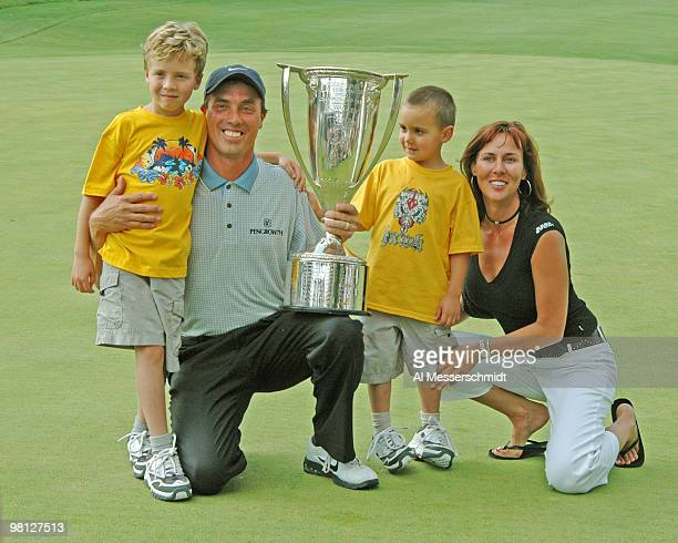 Stephen Ames' family Justin Ryan and Jodi pose on the 18th green with the winner's trophy at the Cialis Western Open July 4 2004 in Lemont Illinois