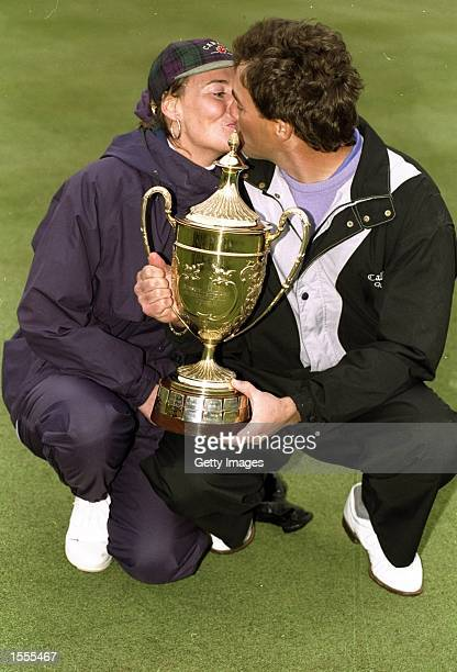 Stephen Ames of Trinidad and Tobago kisses his wife as he poses with the trophy after his victory in the Benson and Hedges International Open at the...
