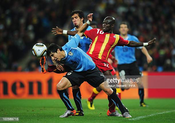 Stephen Appiah of Ghana tries to control the ball as Jorge Fucile of Uruguay attempts to head the ball during the 2010 FIFA World Cup South Africa...