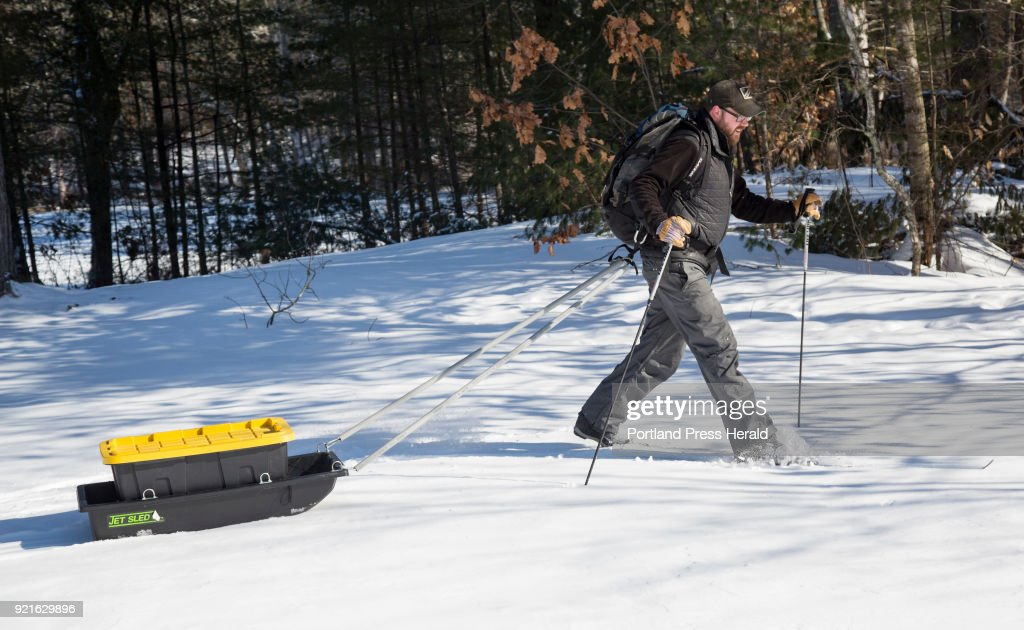 Stephen Bailey demostrates the use of a home-made winter camping sled he designed to attach to a backpack and can be pulled behind.