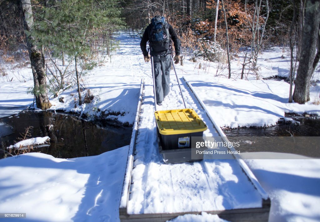 Stephen Bailey demostrates the use of a home-made winter camping sled he designed while crossing a stream in Windham.