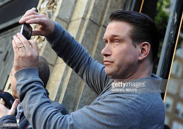 Stephen Baldwin takes a picture as his brother Alec Baldwin poses with his Star on the Walk of Fame in Hollywood California on February 14 2011 AFP...