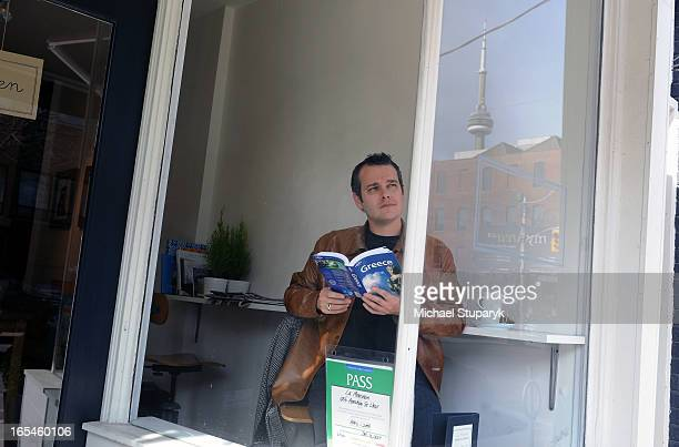 Stephen Brown is planning for a trip to Greece based on his Aeroplan miles sitting in a cafe looking at a travel book CN Tower reflected in window to...