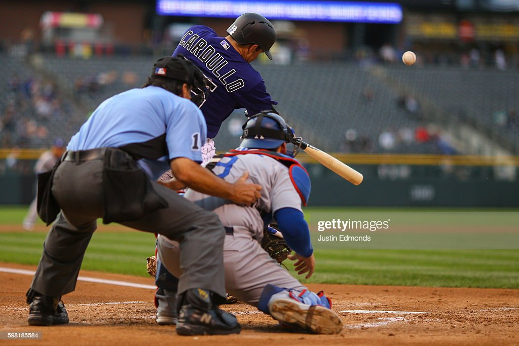 Stephen Cardullo #65 of the Colorado Rockies hits a grand slam as umpire Phil Cuzzi and catcher Yasmani Grandal #9 of the Los Angeles Dodgers look on during the first inning at Coors Field on August 31, 2016 in Denver, Colorado. This is Cardullo's second home home run of his career. He also hit a solo shot in the first game of the double header.