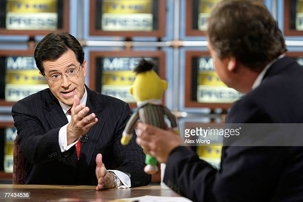 Stephen Colbert host of 'The Colbert Report' speaks as moderator Tim Russert holds up the Sesame Street figure Bert during a taping of 'Meet the...