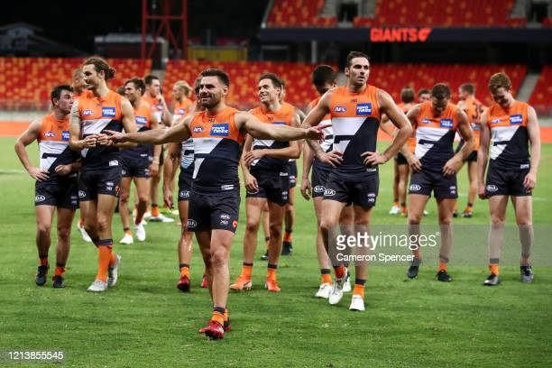 Stephen Coniglio of the Giants and team mates celebrate winning the round 1 AFL match between the Greater Western Sydney Giants and the Geelong Cats...