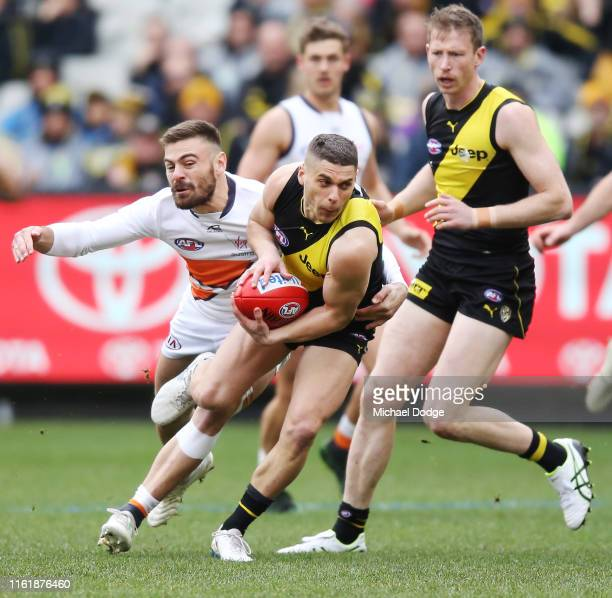 Stephen Coniglio of the Giants chases Dion Prestia of the Tigers before he injured his leg during the round 17 AFL between the Richmond Tigers and...