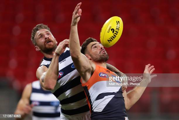 Stephen Coniglio of the Giants is challenged by Zach Tuohy of the Cats during the round 1 AFL match between the Greater Western Sydney Giants and the...