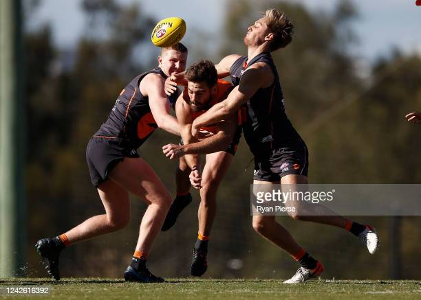 Stephen Coniglio of the Giants is tackled by Tom Green and Jackson Hately of the Giants during a Greater Western Sydney Giants AFL training session...