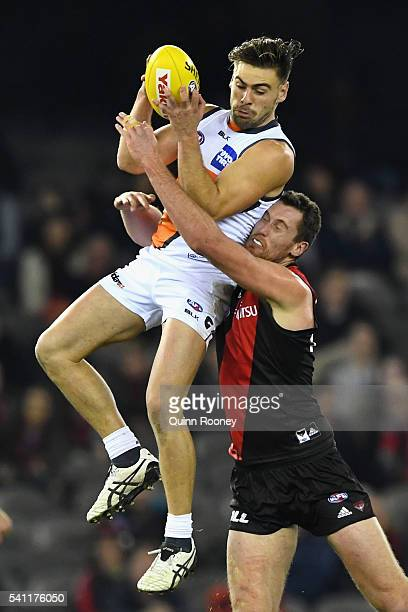 Stephen Coniglio of the Giants marks infront of Matthew Leuenberger of the Bombers during the round 13 AFL match between the Essendon Bombers and the...