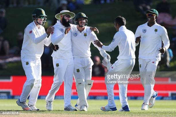 Stephen Cook Hashim Amla and Quinton de Kock of South Africa celebrate the dismissal of Henry Nicholls of New Zealand during day two of the First...