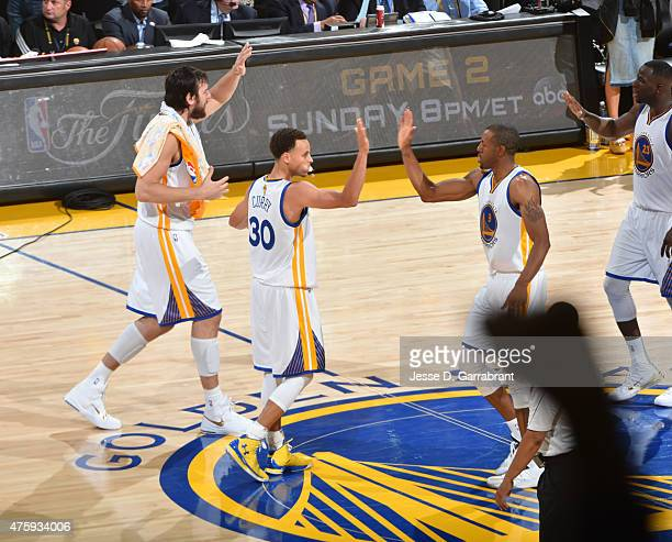 Stephen Curry and Andre Iguodala of the Golden State Warriors give each other high fives after winning the game against the Cleveland Cavaliers at...