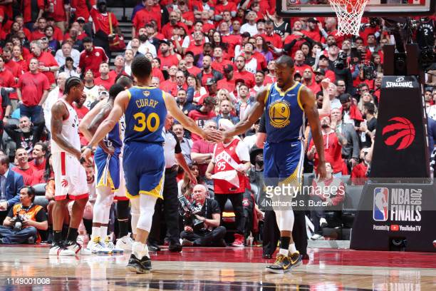 Stephen Curry and Andre Iguodala of the Golden State Warriors high five against the Toronto Raptors during Game Five of the NBA Finals on June 10,...