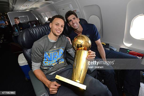 Stephen Curry and Bob Myers of the Golden State Warriors holds the NBA trophy on the plane as the team travels home from Cleveland after winning the...