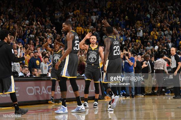 Stephen Curry and Draymond Green of the Golden State Warriors highfive during a game against the LA Clippers on December 23 2018 at ORACLE Arena in...